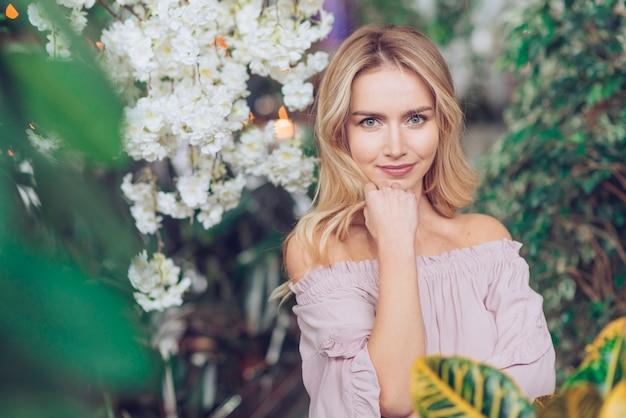 Porträt der recht blonden jungen frau, die im stoff steht