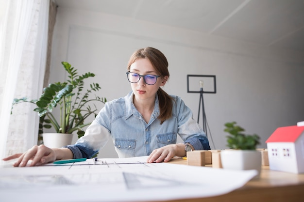 Porträt der recht jungen frau, die an plan am arbeitsplatz arbeitet