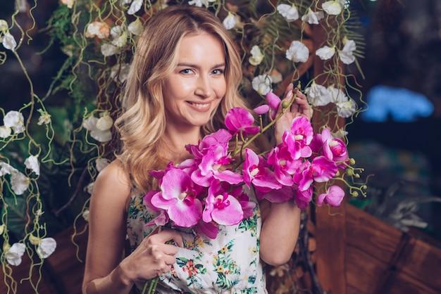 Porträt der recht jungen frau, die in der hand rosa orchideen hält