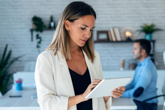 Porträt der recht jungen geschäftsfrau, die mit digitaler tablette arbeitet. im hintergrund ihre kollegen im büro.