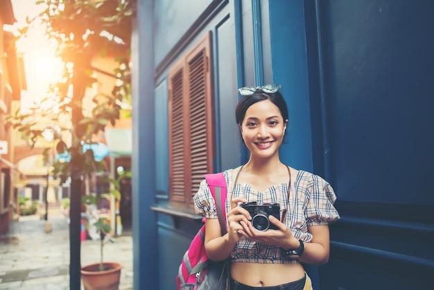 Porträt der recht jungen hippie-frau, die spaß in der stadt mit kamera hat