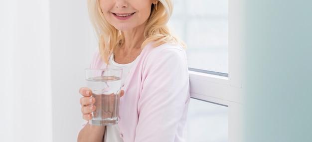 Porträt der recht reifen frau, die ein glas wasser hält