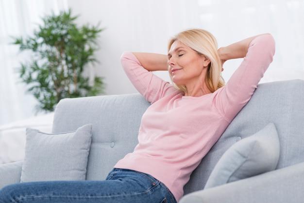 Porträt der recht reifen frau, die sich zu hause entspannt