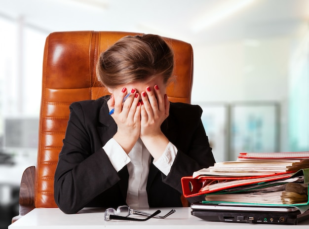 Porträt der reifen enttäuschten geschäftsfrau, die am schreibtisch im büro sitzt