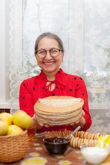 Porträt der reifen frau am tisch mit stapel pfannkuchen und tee