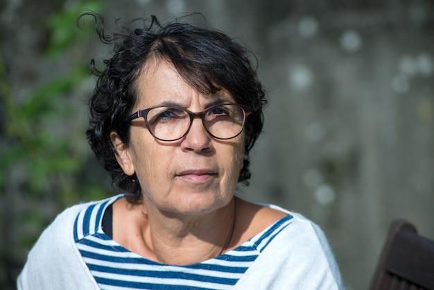 Porträt der reifen frau des brunette mit brillen