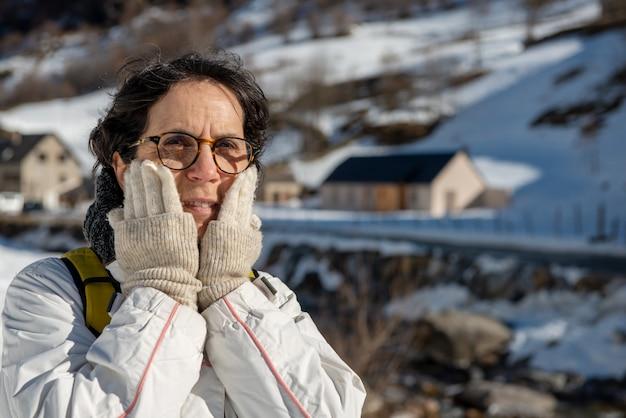 Porträt der reifen frau des wanderers im schnee