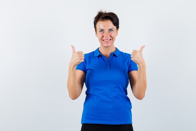 Porträt der reifen frau, die doppelte daumen oben im blauen t-shirt zeigt und selbstbewusste vorderansicht schaut