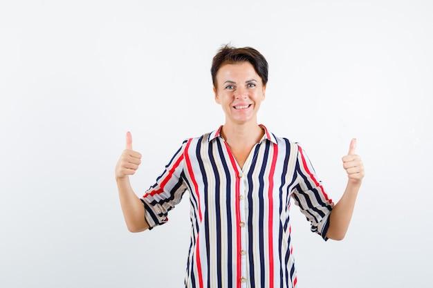 Porträt der reifen frau, die doppelte daumen oben im gestreiften hemd zeigt und glückliche vorderansicht schaut