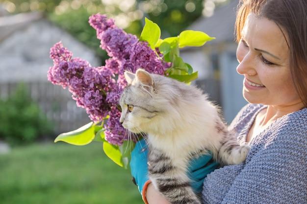 Porträt der reifen frau, die graues flauschiges katzenhaustier in ihren armen hält