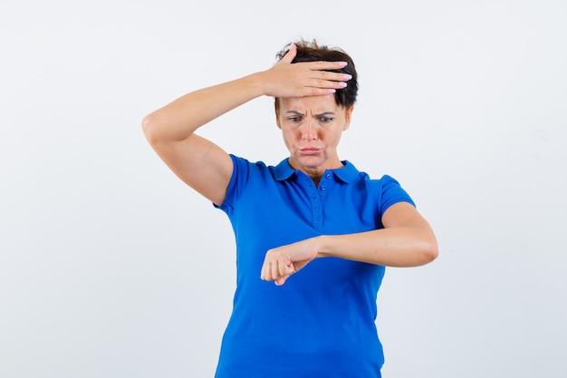 Porträt der reifen frau, die vorgibt, uhr auf ihrem handgelenk im blauen t-shirt zu betrachten und alarmierte vorderansicht zu schauen