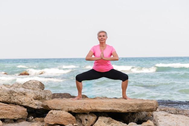 Porträt der reifen frau, die yoga auf dem seeweg tut