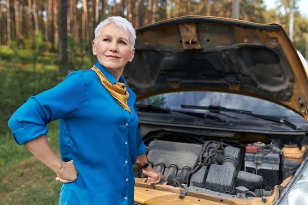 Porträt der reifen frau mit blonden kurzen haaren, die frustrierten gesichtsausdruck haben, weil auto in gebrochen ist. gestresste frau mittleren alters, die nach fahrzeugpanne auf service wartet und motorhaube öffnet