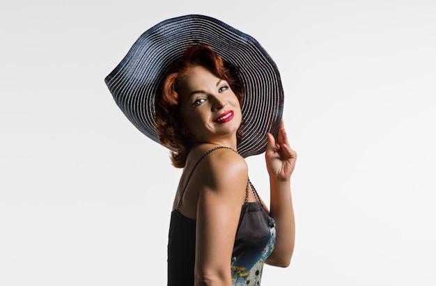 Porträt der reifen frau mit dem roten haar und hut