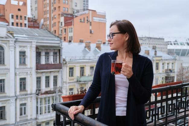 Porträt der reifen frau mit der tasse tee, die auf balkon im freien steht