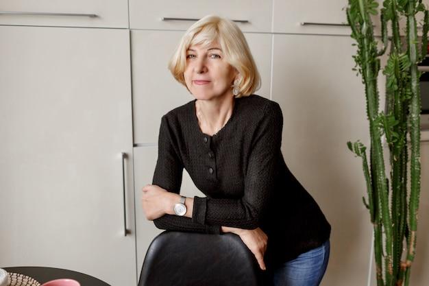 Porträt der reifen gesunden schlanken frau, die in ihrer modernen küche aufwirft