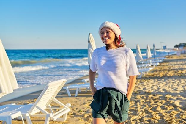 Porträt der reifen glücklichen frau im weihnachtsmannhut auf dem strandseebad