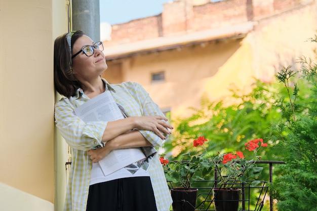 Porträt der reifen hausfrau frau mit magazin auf offenem balkon mit grünen pflanzen verziert