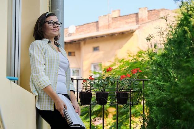 Porträt der reifen hausfrau frau, weiblich mit magazin auf offenem balkon Premium Fotos