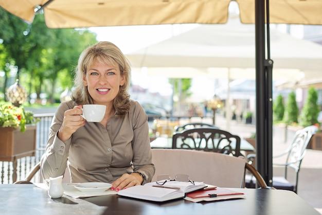Porträt der reifen schönen blonden frau, die seitlich schaut, kopienraum. lächelnde geschäftsfrau mittleren alters, die kaffee in einem café im freien trinkt