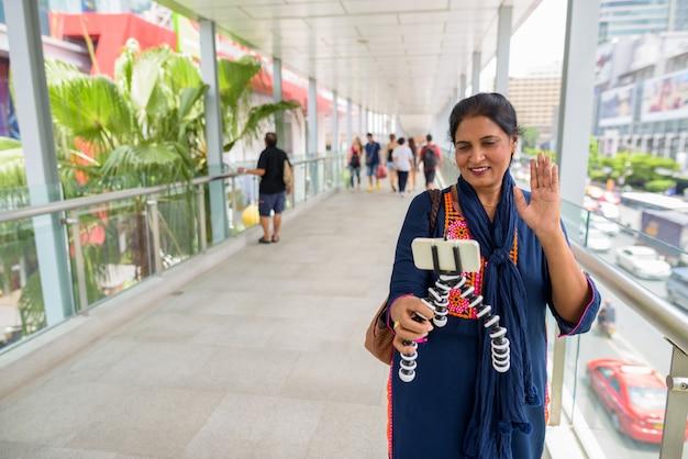 Porträt der reifen schönen indischen frau, die die stadt bangkok, thailand erkundet
