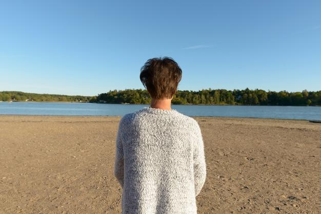 Porträt der reifen schönen skandinavischen frau gegen schöne landschaft des ufers