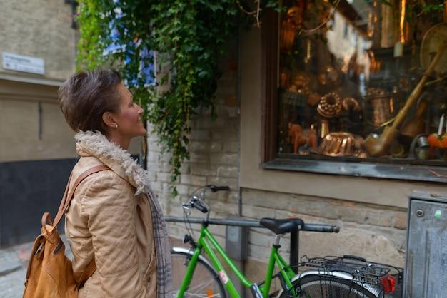 Porträt der reifen schönen skandinavischen touristenfrau mit den kurzen haaren, die durch die stadt stockholm in schweden reisen