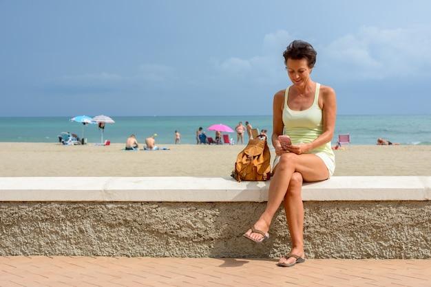 Porträt der reifen schönen touristenfrau am strand im freien