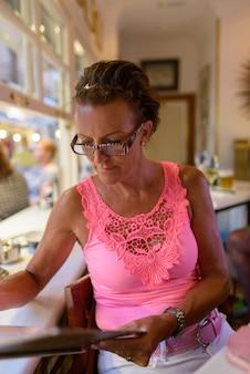 Porträt der reifen schönen touristenfrau, die innerhalb des restaurants in spanien sitzt