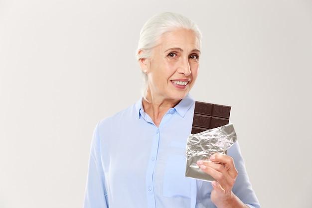 Porträt der reizenden alten dame, die schokoriegel hält