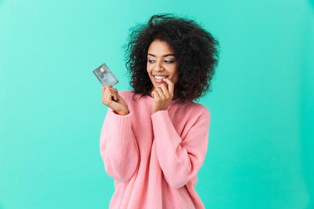 Porträt der reizenden amerikanischen frau 20s mit afro-frisur, die plastikkreditkarte mit vergnügen hält, lokalisiert über blaue wand