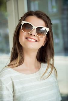 Porträt der reizenden erfreuten jungen frau in der modischen brille, die an der kamera aufwirft