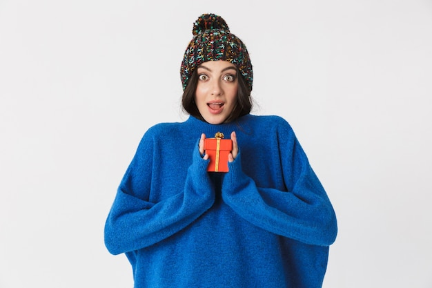 Porträt der reizenden frau, die wintermütze hält geschenkbox während des stehens trägt, lokalisiert auf weiß