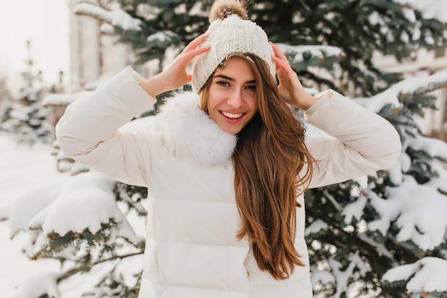 Porträt der reizenden frau mit dem langen hellbraunen haar, das wahre glückliche gefühle am wintertag auf tannenbaum zeigt. charmante junge frau in der weißen jacke, die am kalten morgen im verschneiten park herumalbert.