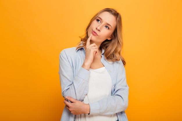Porträt der reizenden frau mit kastanienbraunem haar, das beiseite schaut, tief in den gedanken ist und nachdenkliche geste tut, lokalisiert über gelbem hintergrund