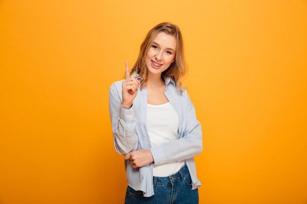 Porträt der reizenden frau mit kastanienbraunem haar, das zeigefinger auf copyspace-text oder produkt zeigt, lokalisiert über gelbem hintergrund
