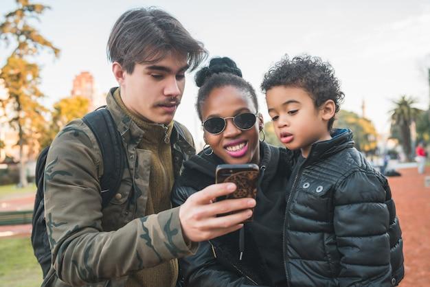 Porträt der reizenden gemischten ethnischen familie, die spaß hat, sich entspannt und handy im park im freien benutzt.