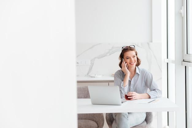 Porträt der reizenden glücklichen brünetten frau, die auf handy spricht, während sie sitzt und tasse heißen tee hält, drinnen