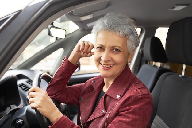 Porträt der reizenden glücklichen reifen frau mit den kurzen grauen haaren, die im fahrersitz sitzen
