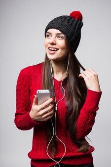 Porträt der reizenden jungen frau, die musik unter verwendung der kopfhörer genießt, lokalisiert über weißer wand
