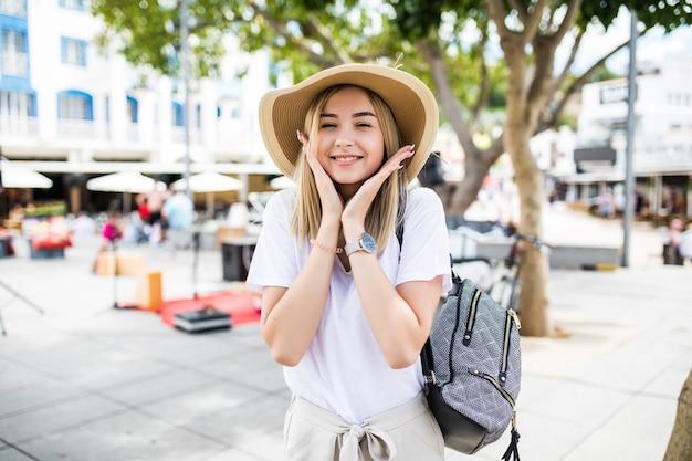 Porträt der reizenden jungen frau mit dem zahnigen strahlenden lächeln, das kamera betrachtet, die das kinn berührt