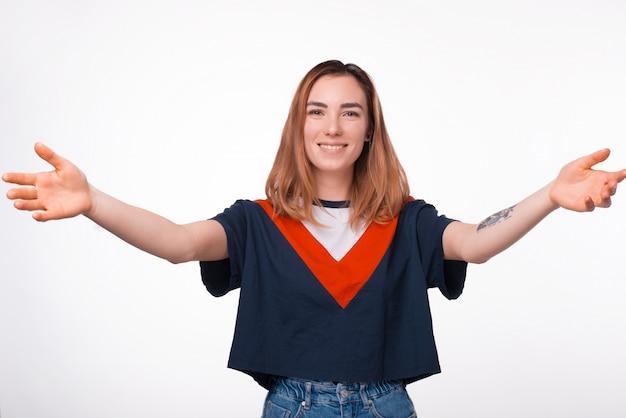 Porträt der reizenden jungen hipsterfrau, die willkommene geste macht, offene hände