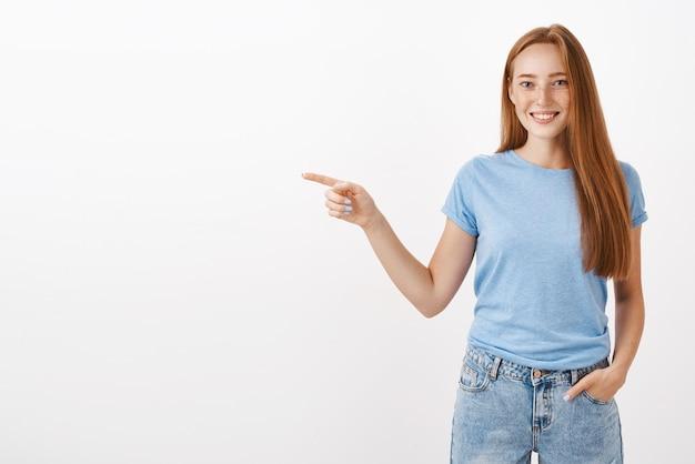 Porträt der reizenden jungen rothaarigen frau mit sommersprossen, die hände in der tasche halten und mit freudigem höflichem lächeln nach links zeigen