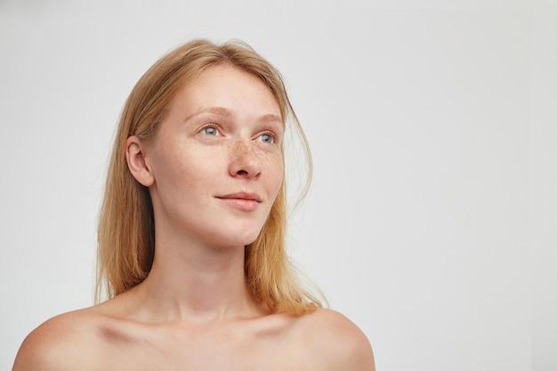 Porträt der reizenden jungen rothaarigen langhaarigen frau mit lässiger frisur, die ruhig beiseite schaut und ihre lippen gefaltet hält und über weißer wand aufwirft