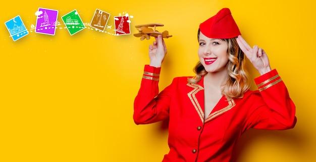 Porträt der reizenden vintagen stewardess, die in der roten uniform mit hölzernem flugzeug trägt. auf grauem hintergrund isoliert.