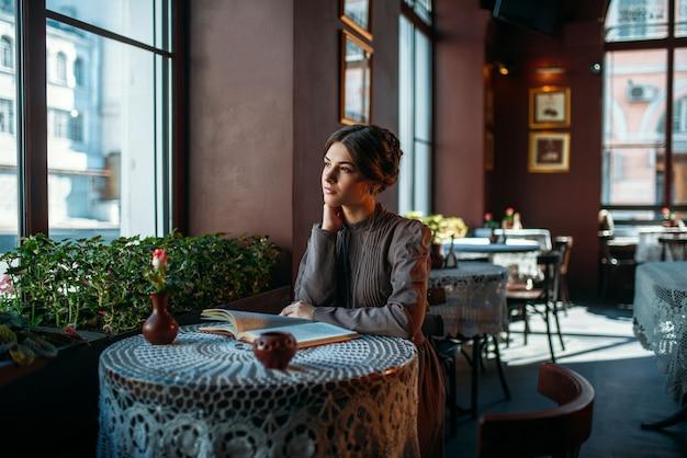 Porträt der retro-art dame, die mit buch sitzt