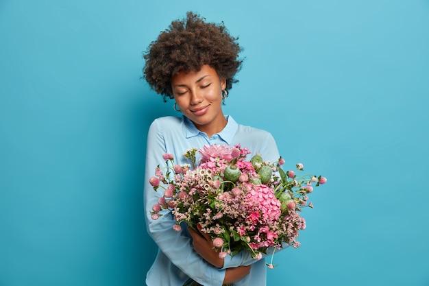 Porträt der romantischen jungen frau umarmt hübsche blumen, bekommt blumenstrauß vom heimlichen bewunderer, fühlt sich berührt, steht mit geschlossenen augen, trägt blaue kleidung