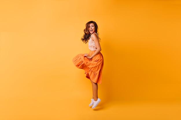 Porträt der romantischen schönen dame im orangefarbenen rock in voller länge. stilvolles sorgloses mädchen, das auf gelb springt.