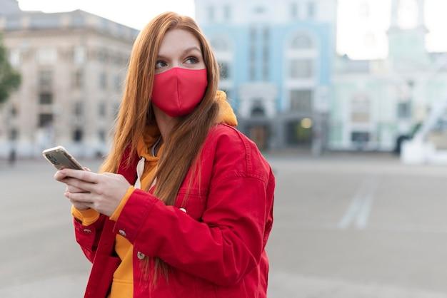 Porträt der rothaarigen frau, die ihr telefon überprüft