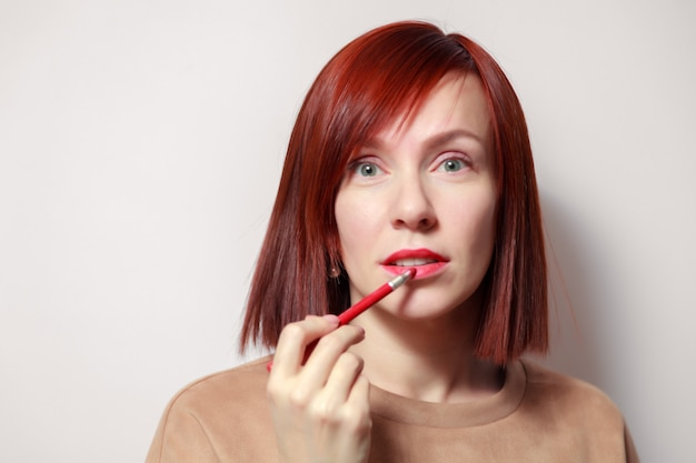 Porträt der rothaarigen hübschen frau malt ihre lippen mit rotem bleistiftlippenstift